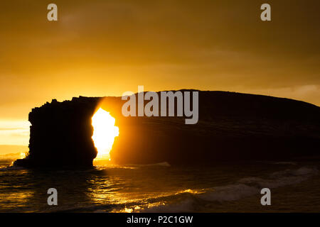 sunset at las catedrales beach in the north sea in Spain. Silhouette image of a rock structure at the beach - Stock Photo