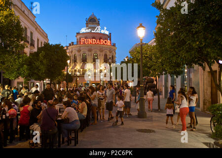 People at tables and in the street in the evening in the Calle Larga, Jerez de la Frontera, Andalusia, Spain, Europe - Stock Photo
