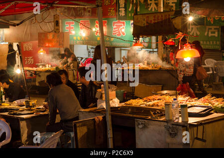 People eating at the food stands at the night market in the city of Kaili, province of Guizhou, China - Stock Photo