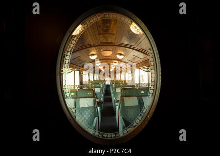 View through a decorated door window into one of the historic wagons of the Golden Pass Railway travelling on the Montreux-Berne - Stock Photo