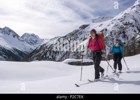 Two female backcountry skiers ascending in fresh snow, summit of Mont Collon, Val d'Herens in the background, Pennine Alps, cant - Stock Photo