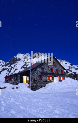 Full-moon over the Grialetsch hut 2542 m with Piz Radoent 3065 m and a carousel of stars above it, Grisons, Switzerland, Europe - Stock Photo