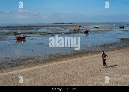 Man jogging along an empty beach at low tide, with boats and southend on sea pier, in the background. - Stock Photo