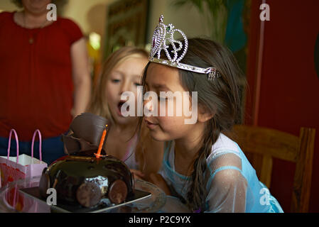 Cute little preteen Asian girl wearing a princess dress and a tiara blowing out the candles on her birthday cake with her best friend sitting with her - Stock Photo