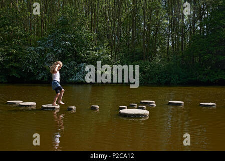 Young preteen girl walking across a stone path in the middle of a river trying out this challenge to find her path across without falling in the water - Stock Photo