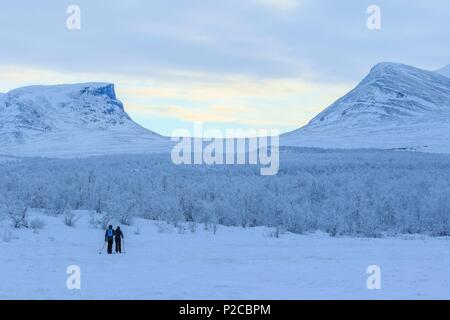 Sweden, Lapland, region listed as World Heritage by UNESCO, Norrbotten County, ski walkers on the Kungsleden in winter with the Lapporten in the background in the Abisko National Park - Stock Photo