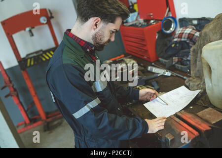 Mechanic reading instruction manual in repair garage - Stock Photo