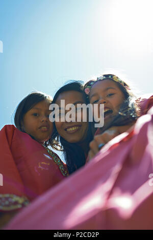 Malay mother and her two young daughters wearing traditional Baju Kurung dresses smiling happily into camera during Hari Raya celebration - Stock Photo