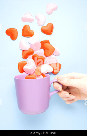 Creative concept photo of hand holding coffee cup with hearts on blue background. - Stock Photo