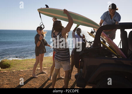 Group of friends removing surfboard from jeep - Stock Photo