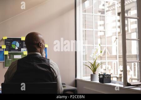 Senior graphic designer relaxing in office - Stock Photo