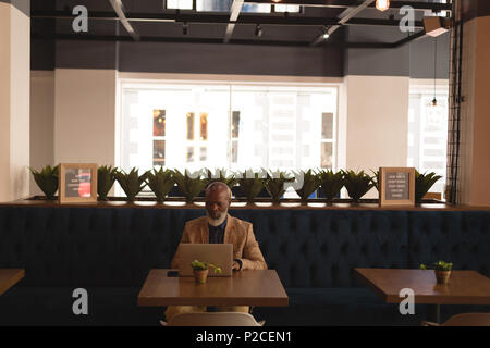 Senior graphic designer using laptop in cafeteria - Stock Photo