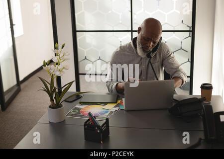 Senior graphic designer talking on mobile phone at desk - Stock Photo
