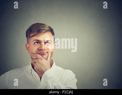 Handsome pensive man holding hand on chin and thinking thoroughly while looking up on gray - Stock Photo