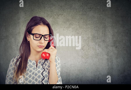 Pretty girl in glasses looking down in sadness while speaking on phone and having problems - Stock Photo