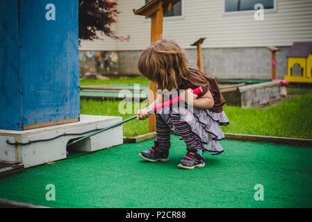 A young girl plays miniature golf in warmer weather. - Stock Photo