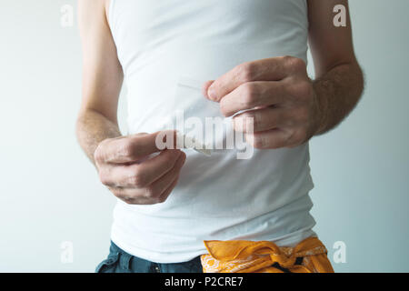 Gang member and drug dealer offering crack cocaine in small plastic bag, close up of hands with selective focus - Stock Photo