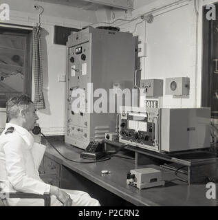 1950s, historical, on a passenger liner in the radio room, a uniformed male wireless or radio operator at his desk speaking on a telephone using the communications equipment of the era. The operator's primary role was 'safety at sea'. - Stock Photo