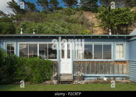 Front on shot of beach house / bach. old timbers. windows. garden. Historic Pourerere Bach / Beach House, Hawke's Bay, New Zealand with new addition b - Stock Photo