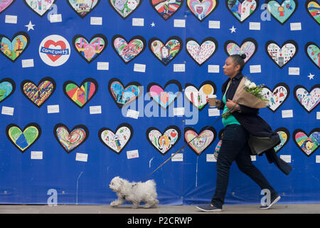 Local residents on the first anniversary of the Grenfell tower block disaster where local schoolchildren have drawn pictures and messages, on 14th June 2018, in London, England. 72 people died when the tower block in the borough of Kensington & Chelsea were killed in what has been called the largest fire since WW2. The 24-storey Grenfell Tower block of public housing flats in North Kensington, West London, United Kingdom. It caused 72 deaths, out of the 293 people in the building, including 2 who escaped and died in hospital. Over 70 were injured and left traumatised. A 72-second national sile - Stock Photo