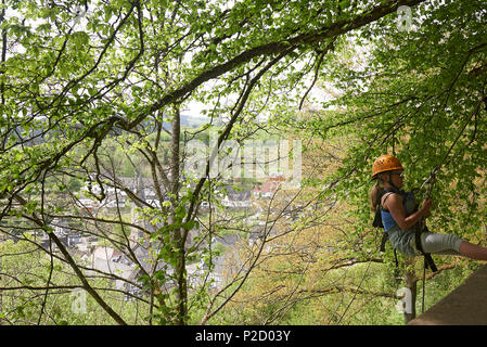 Young preteen girl trying out abseiling down a wall on a mountain with a village far away in the background - Stock Photo