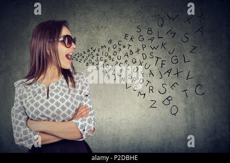 Woman in sunglasses talking with alphabet letters coming out of her mouth. Communication, information, concept - Stock Photo