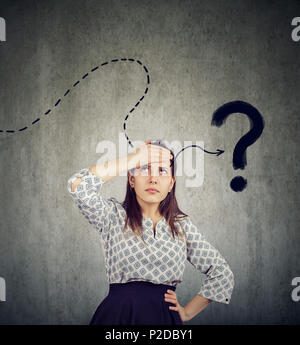 Young woman thinking hard trying to remember has a question - Stock Photo