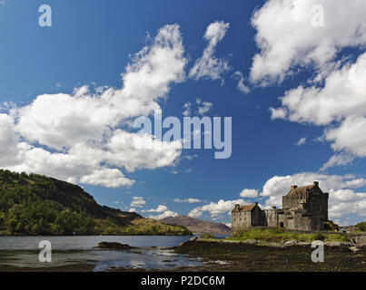 Dornie, Scotland - May 12th, 2018 - Eilean Donan Castle with a clear blue sky and fluffy white clouds - Stock Photo