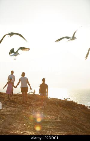 Young family walking along the steep coast, Rota Vicentina, Portugal - Stock Photo