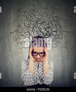 Girl in glasses having problems with mental health and looking deep in chaos on gray background - Stock Photo