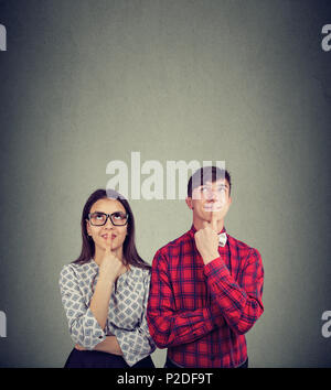 Charming girl and man holding fingers on lips and creating plans for future together standing on gray background. - Stock Photo