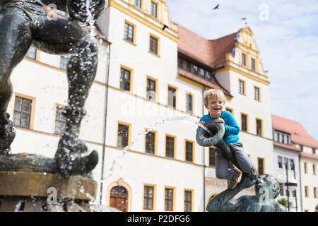 Boy sitting on the fountain outside the town hall, Torgau, Saxony, Germany, Europe - Stock Photo