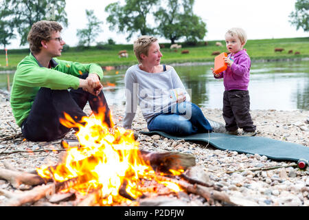 Family sitting around the campfire, Camping along the river Elbe, Family bicycle tour along the river Elbe, adventure, from Torg - Stock Photo