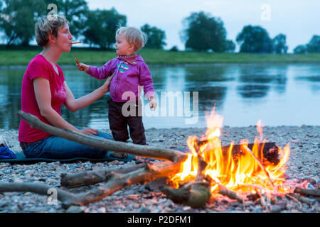 Mother and daughter making bread on a stick on the campfire, Camping along the river Elbe, Family bicycle tour along the river E - Stock Photo