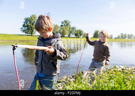 Boys fishing, Family bicycle tour along the river Elbe, adventure, from Torgau to Riesa, Saxony, Germany, Europe - Stock Photo