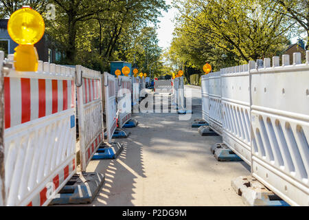 red and white barricades with warning lights on a street in a residential area - Stock Photo