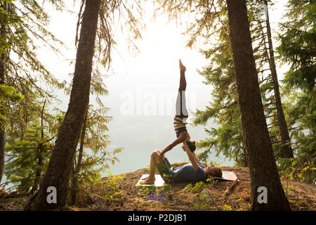 Sporty couple practicing acro yoga in a lush green forest - Stock Photo