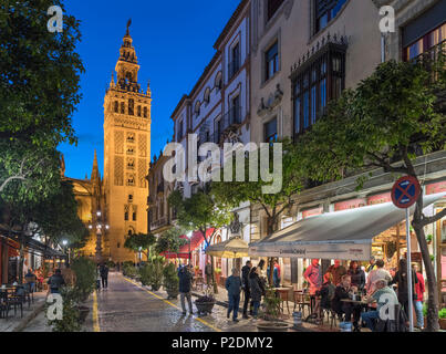 Seville, Spain. Cafes on Calle Mateos Gago at night looking towards the Giralda tower and Cathedral, Barrio Santa Cruz, Sevilla, Andalucia, Spain - Stock Photo