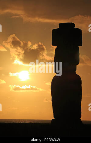 Silhouette of Moai statue against beautiful sunset sky at Ahu Tahai, Easter Island, Chile - Stock Photo