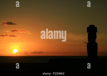 Stunning view of the sun setting over Pacific ocean with Moai's silhouette at Ahu Tahai, Easter Island, Chile - Stock Photo