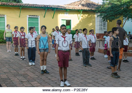 Cuban school children lined up in square being addressed by a teacher. Trinidad, Cuba. - Stock Photo