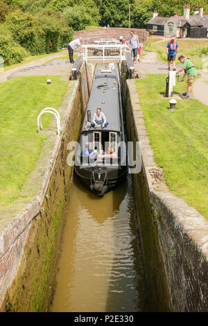 A narrow boat entering a lock to ascend the flight of locks at Foxton - Stock Photo