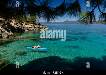 Woman stand up paddle boarding on the crystal clear blue waters of Lake Tahoe in Incline Village, Nevada, North America. - Stock Photo