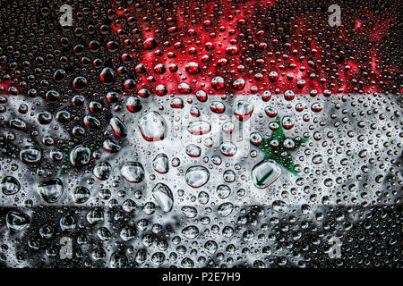 Close-up of a drop of water against a background of the national flag of  Syria on an isolated background - Stock Photo