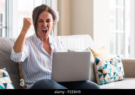 Middle aged woman using laptop in the sofa annoyed and frustrated shouting with anger, crazy and yelling with raised hand, anger concept - Stock Photo