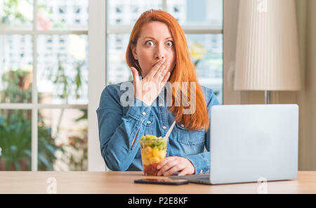 Redhead woman using computer laptop eating fruit at home cover mouth with hand shocked with shame for mistake, expression of fear, scared in silence,  - Stock Photo