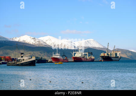 The Saint-Christopher, an old boat, lies in the bay of Ushuaia. Behind that are a few container ships who show some small harbor activity. - Stock Photo