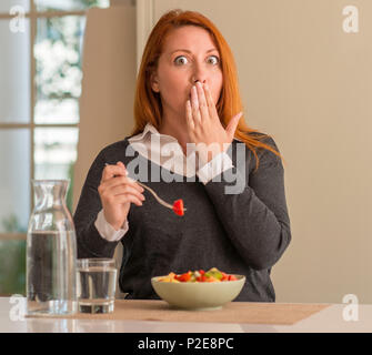 Redhead woman eating fruit bowl, kiwi and strawberry at home cover mouth with hand shocked with shame for mistake, expression of fear, scared in silen - Stock Photo