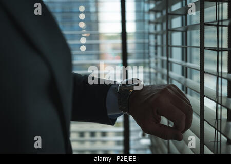 Businessman checking time on wrist watch - Stock Photo