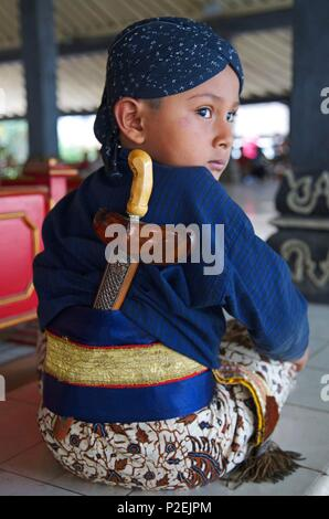 Indonesia, Java, Ijen, Young son of a guard of the kraton, the royal palace of the ancient Sultanante of Yogyakarta, in traditional dress and wearing a kriss the dagger of ceremony - Stock Photo